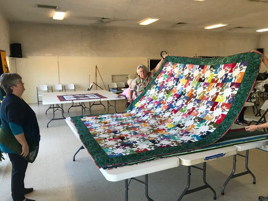 Karen Kendo examines a quilt as she judges entries