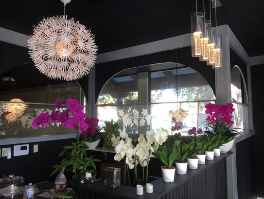 Orchids and decorative light fixtures are seen at the