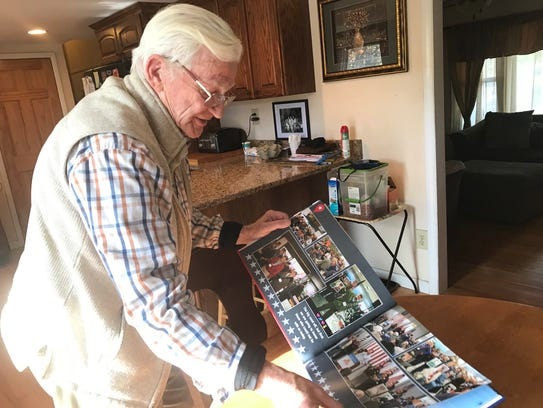Thom Usher, a veteran, shows a book that his family