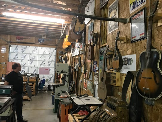 Dan'l Brazinski looks over his wall of antique guitars.