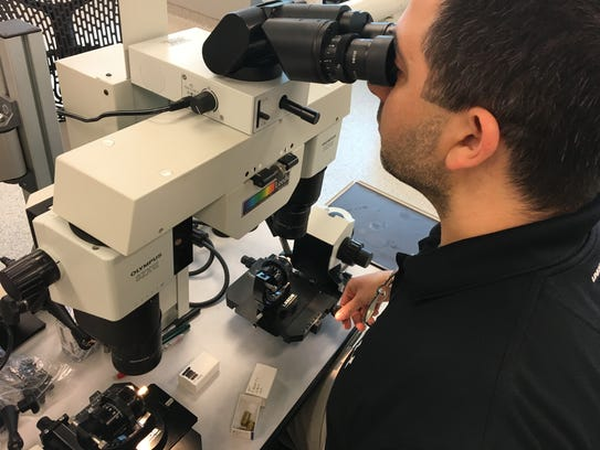 Forensic scientist Mark Boackle works with firearms