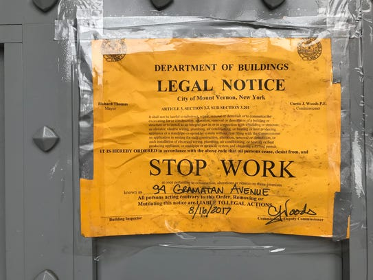 A stop-work order posted on the front door of Sue's