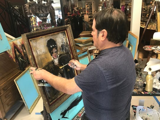 Artist Franco Mondini-Ruiz uses a paint brush, his fingers and other materials to create pieces of art he's selling to customers of Casa Authentique through Thursday.
