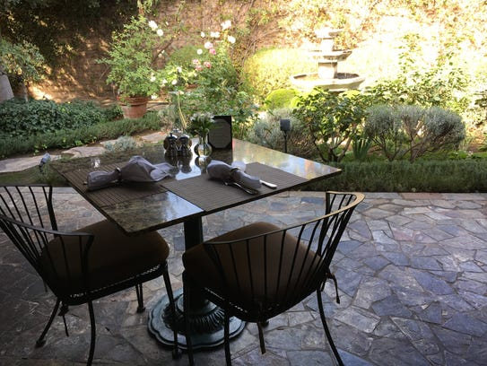 A patio table offers views of the rose garden and water