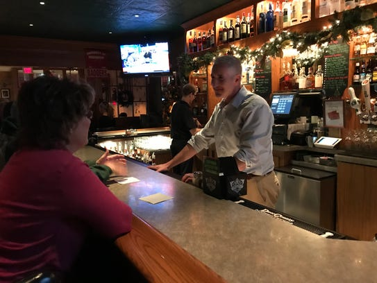 Rich Loch, owner of Ricardo's Pizza, talks with some