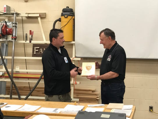Grafton technical education teacher Kevin Gain (left) presents Harold Klug with a plaque honoring Klug for his service to the school's technical education program.