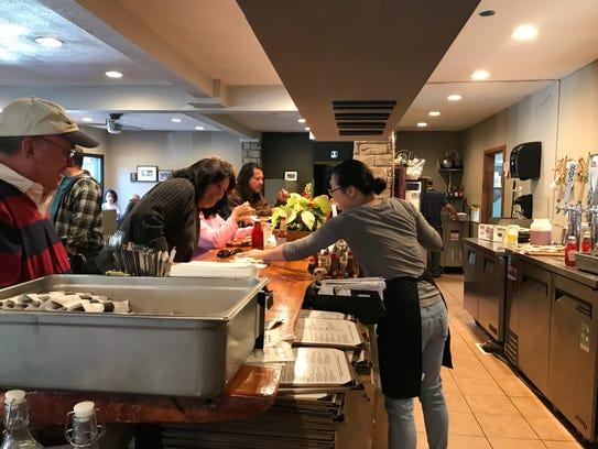 Server Grace Han helps diners at The High Cafe restaurant