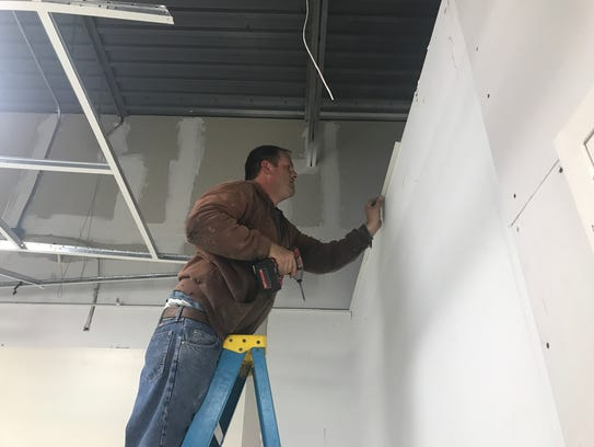 Brian Brittingham fixes the ceiling inside the Eastern