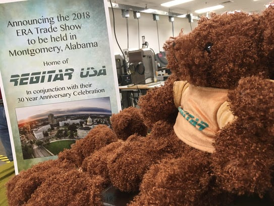 A stuffed animal sits next to a trade show announcement