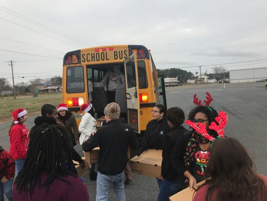 Volunteers load 200 boxes of food into a school bus