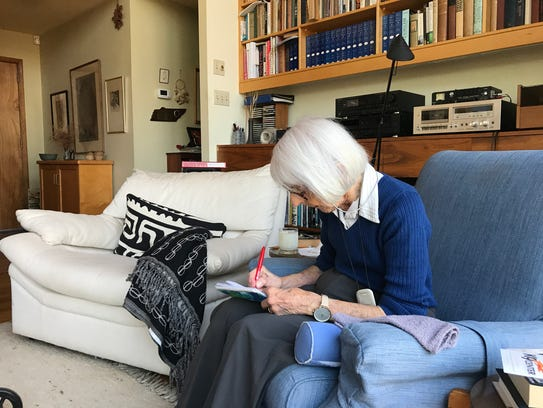 Liane Russell writes out a grocery list for her day-time