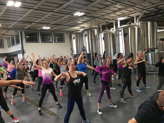 A dance club cardio exercise  class is held inside