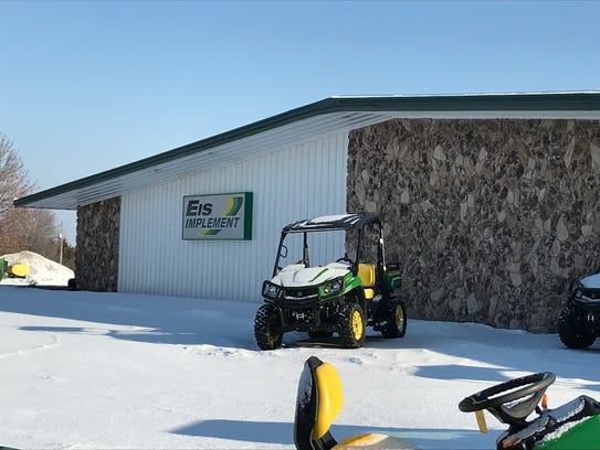 A snow-covered lawnmower sits outside of Eis Implement