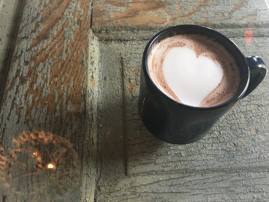 A mug of hot chocolate with a heart pattern at Blue