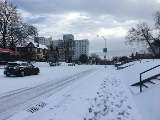 Drivers make their way down a snowy Poplar Avenue in