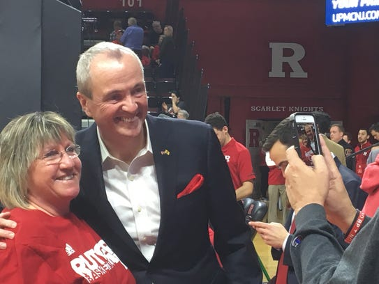 Gov. Phil Murphy poses with a Rutgers fan at halftime.