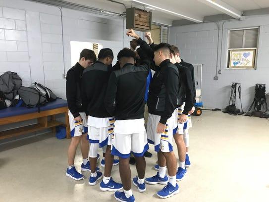 John Carroll Catholic players huddle in the locker