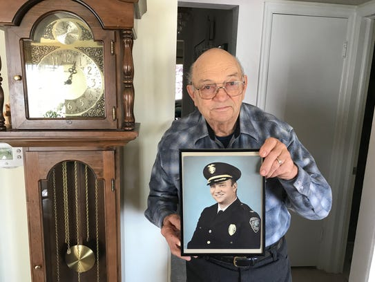 Bill Steele holds of photo of himself in his Great