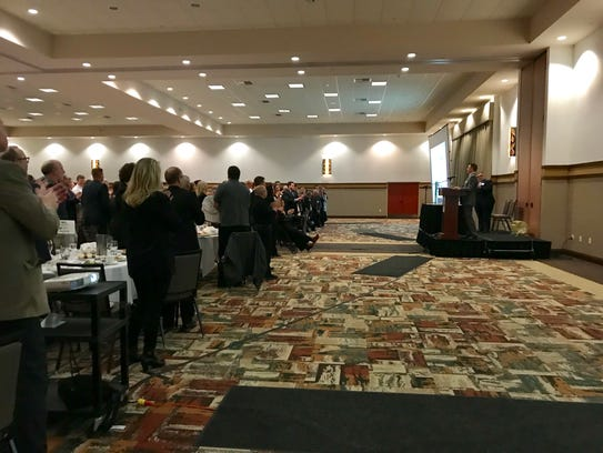 An audience stands to applaud Keith Pilger, a partner