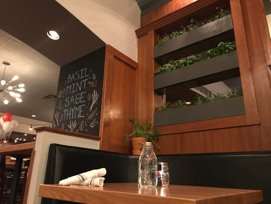 Fresh herbs grow over a table for two at healthy Nook,