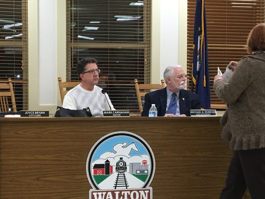 Walton Mayor Mark Carnahan, left, watches as the city