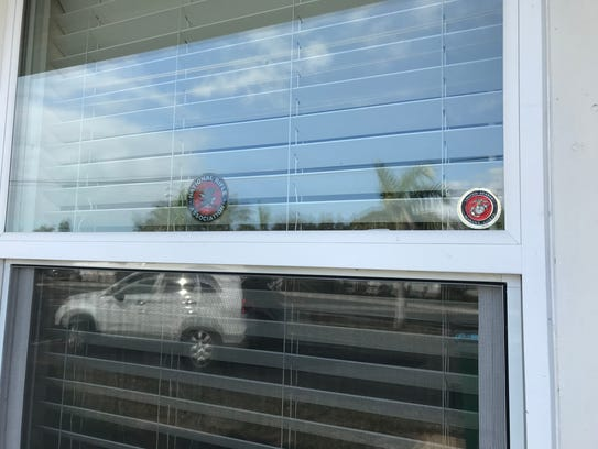 An NRA sticker and a Marine logo grace a window at an apartment building on Skyline Boulevard where a resident was arrested Sunday after Cape Coral police said he shot at a target in his unit with a 9mm handgun, narrowly missing two people sleeping next door.