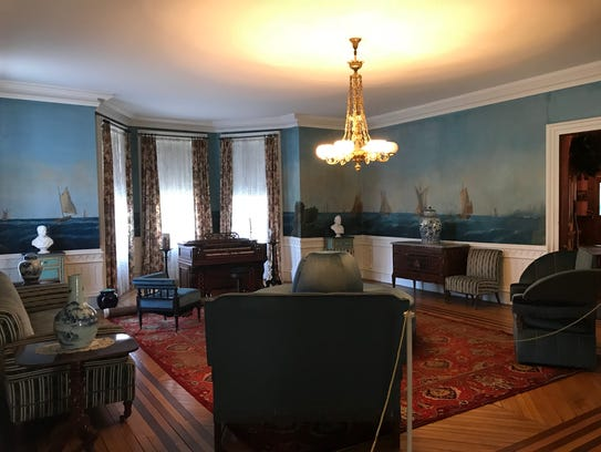 Hand-painted wallpaper adorns a blue-themed sitting