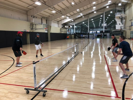 Mark Tauscher, left, in red hat, plays pickleball at