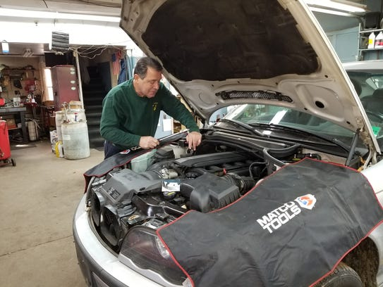 David Tullo works under the hood of a car at Tull's