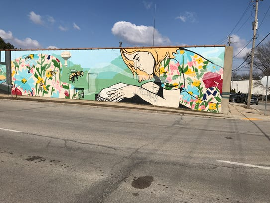 A mural of flowers, honeybees and a child reading a