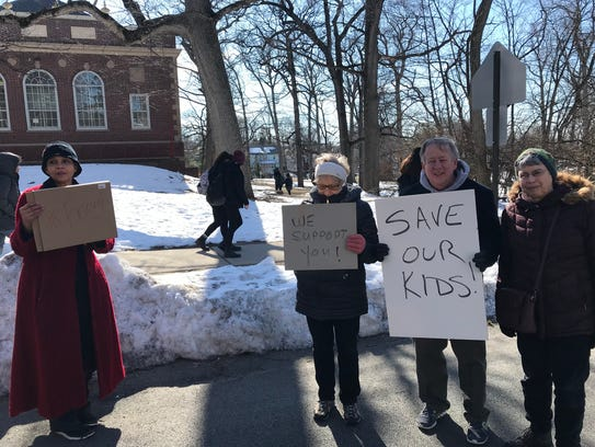 Residents stand outside the Montclair High School amphitheater displaying their support for MHS students participating in a walkout on Wednesday, March 14.