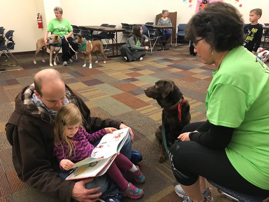 Ava Hutsell, 4, reads with her father, Joel Hutsell, while chocolate lab Layla listens with owner Mattia Bray. The Hutsell family attended the Abilene Public Library's Read To A Dog Day at the Mockingbird branch Wednesday.