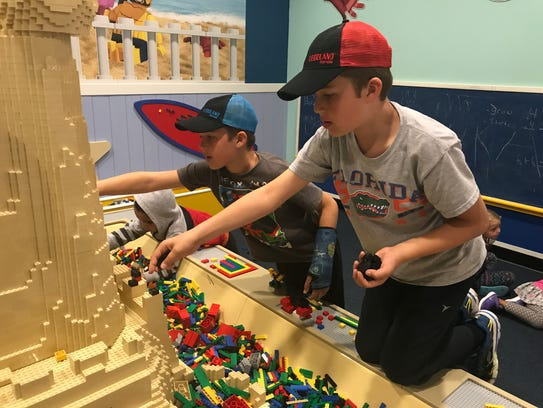 Connor and Adam Blandford, 9, play with Legos in a