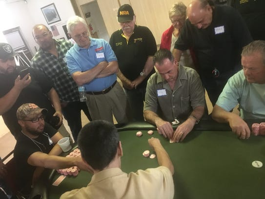 Poker champion Carlos Mora, seated left, plays against