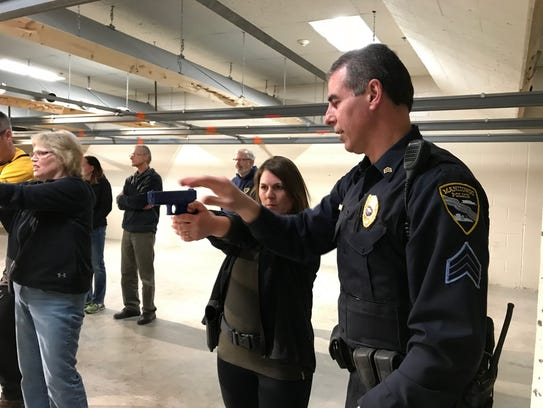 Manitowoc Police Sgt. Bruce Jacobs shows Terri Augustine how to hold a gun during the third week of Citizens Academy class March 20.