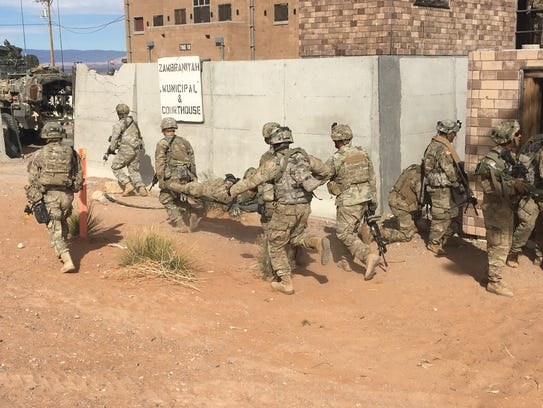 Soldiers take care of a mock casualty during the Iron