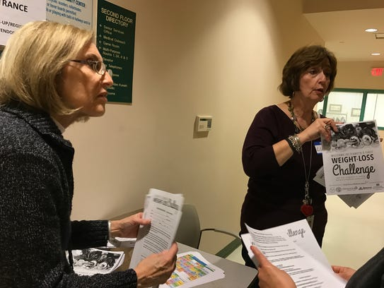 Marla Klein and Linda Lohsen hand out information at
