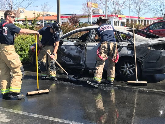Firefighters mop up Tuesday after two parked cars caught