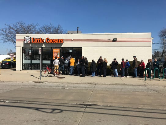 A line coming out the door at a Little Caesars's in