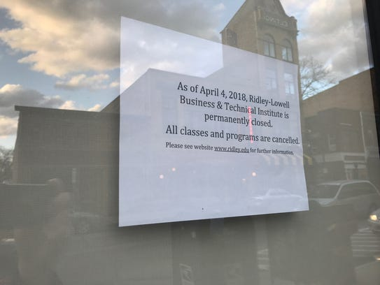 A sign hangs in the school's Main Street location in