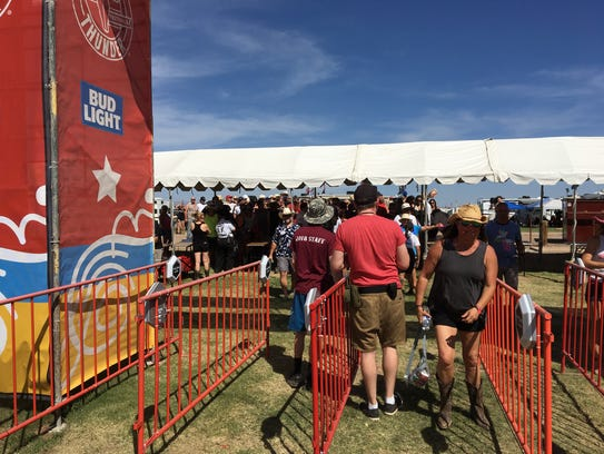 Festival goers scan their wristbands upon entering