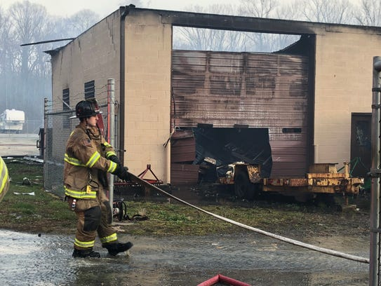 Crews pull water hoses on scene at an Elkton fire on