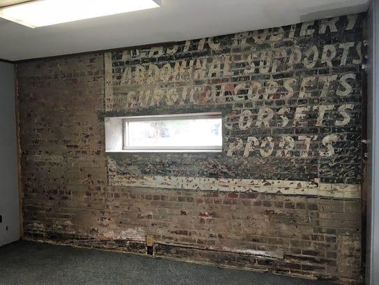 A brick wall concealed by wood paneling at 514 Crockett