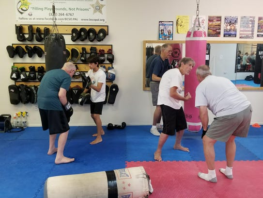 Members hit the bag during a Rock Steady Boxing class