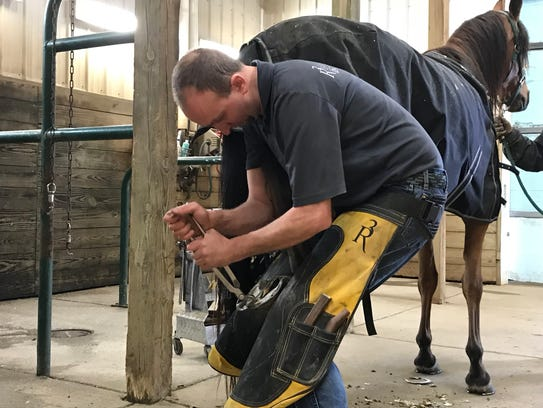 Farrier David Hallock works on the hoof of a horse