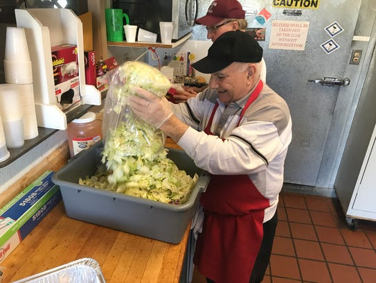 Clemente Suero prepares salad for the IASC fundraiser