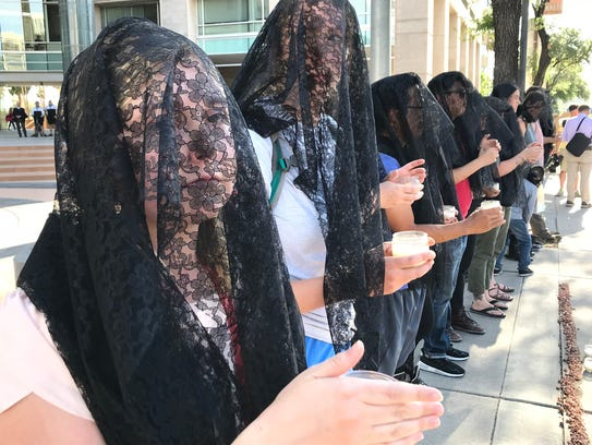 Protesters wear black veils outside Tucson's federal
