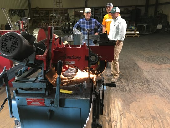 From left, Phil Averitt, Heath Honeycutt and Brandon Clark watch as a machine automatically sharpens a large band saw blade used at Averitt Lumber. Clark Hardwoods recently bought the Houston County sawmill to augment its Macon County operations.