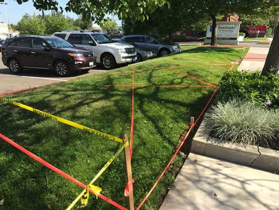 Tape covers a stretch of grass outside a business on