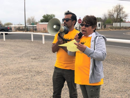 """Somos Un Pueblo Unido spokesman Emmanuelle """"Neza"""" Leal-Sanchez, left, holds the megaphone as Lourdes Morales of Bloomfield, right, speaks during the Rally Against Trump's Deportation Machine Tuesday along County Road 5500 in the Lee Acres area."""